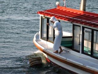 Penyelam Ama melempar bak kayu ke luar kapal terlebih dahulu sebelum ia melompat masuk ke dalam air