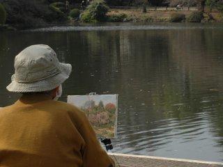 Một nghệ sỹ đang cố gắng ghi lại vẻ đẹp thoáng qua của mùa xuân trên giá vẽ.