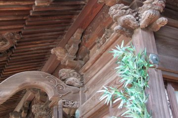 The shrine is decorated with numerous, intricately carved designs in the wood under the peak.