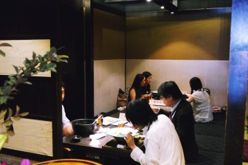 <p>A peak into the back of the restaurant which offers private rooms and several low communal tables</p>