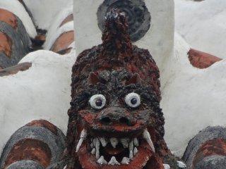 Сиса крадется по традиционной черепичной крыше на острове Такетоми