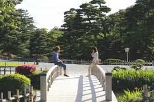 Một cặp đôi tận hưởng ánh nắng chiều trên một trong số những cây cầu trong công viên