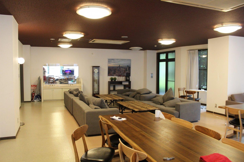 拡張式テーブルの置かれた快適なラウンジ。テレビコーナーやソファもある。人々の憩いの場所だ。
