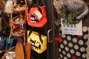 Một cửa hàng trưng bày túi hình mèo và tấm biển tìm nhà cho mèo lạc