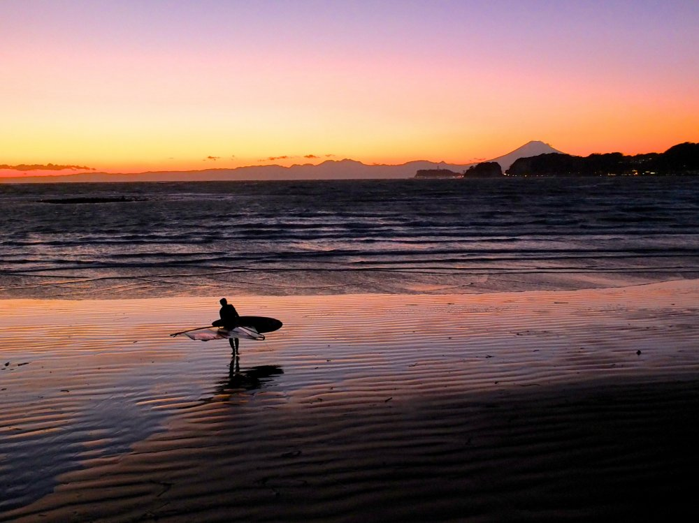 A lonely surfer about to call it a day, Mt. Fuji, and a beautiful sunset