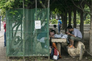 <p>Too old for the mini-themepark? These teens know how to entertain themselves, chowing down yakisoba under the shade.</p>