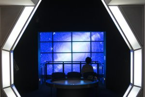A large video screen at the end of the space-themed permanent exhibition section.