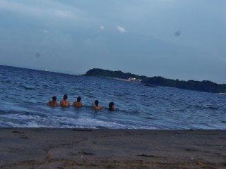 Ces jeunes s'amusent à sauter par-dessus les vagues en se tenant chacun par la main