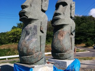 The original moai given to Minamisanriku stand wounded but full of pride at a hill overlooking the town