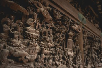 <p>Intricately carved walls based on Lotus Sutra, inside the temple</p>