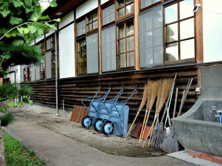 Wheelbarrows and brooms lean against a building's side