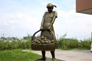 Statue of a girl with a bucket of apples