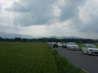 Lalu lintas cukup padat saat itu, padahal pemandangan sekitarnya adalah persawahan.