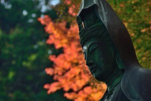 The statue is surrounded by colorful maple leaves