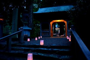 Lanterns in front of and past the temple gate glowing