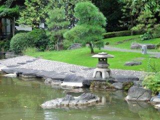 Une lanterne à trois pieds se trouve au bord de l'étang