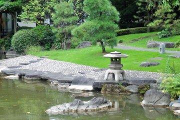 <p>A three-legged lantern sits at the edge of the pond</p>