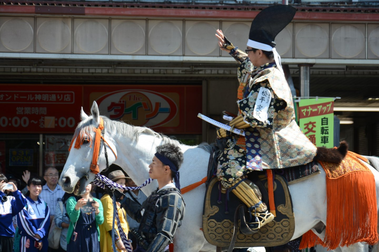 A Samurai being led on horseback.