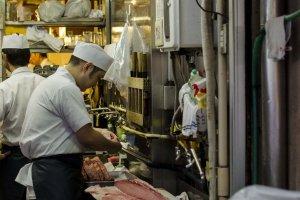 مطعم السوشي ويقوم الشيف بتقطيع السمك لتقديمه