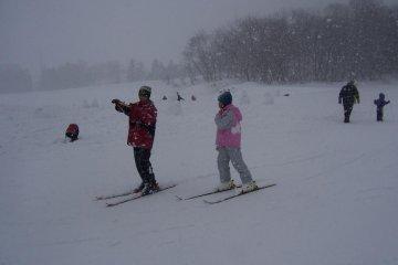 Skiiers being pelted by snowflakes