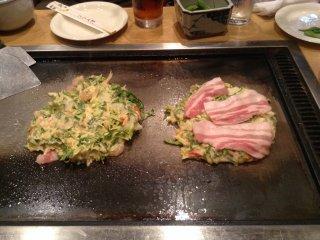 โอะโคะโนะมิยะกิแบบรวมมิตร (อาหารทะเลและเนื้อ) และโอะโคะโนะมิยะกิเนื้หมูบนเตา