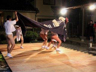 Pertunjukan tarian singa di panggung kecil yang dipasang di pekarangan rumah yang baru dibangun