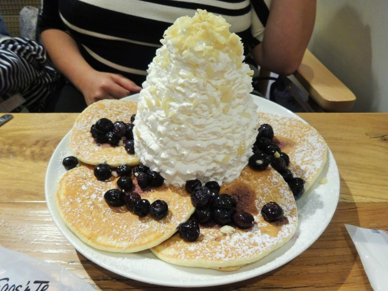 <p>Blueberry pancakes piled high with whipped cream</p>