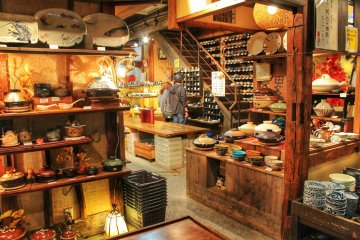 <p>Next to the stairs is a shelf full of different rice bowls</p>