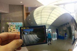 Di bagian hall museum di depan globe perak dan memegang kartu Bendungan Aobashita #1