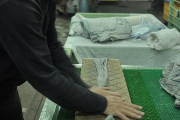 <p>The cloth is rubbed on a specially made wooden board to create small wrinkles</p>