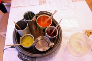 Various liquid wax pots. The pot of clear wax at the bottom was used to finish and seal the candles made