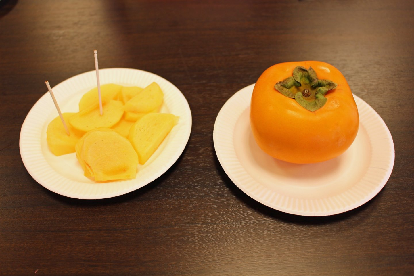 Sliced kaki (Japanese persimmon) next to the real thing. Despite its resemblance to an orange tomato, the kaki have a texture like an apple and taste like something between an apple and a pear.