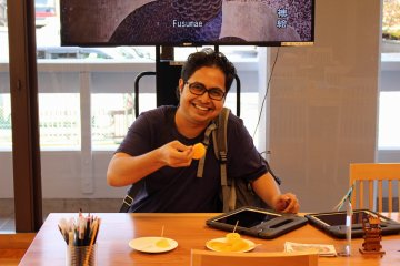 <p>A traveler enjoys a slice of kaki</p>