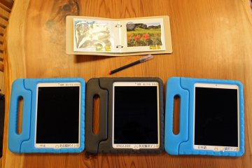 <p>Three of the Visitor Center&#39;s tablets (Chinese, English and Japanese language), and the Asuka Village photo album</p>