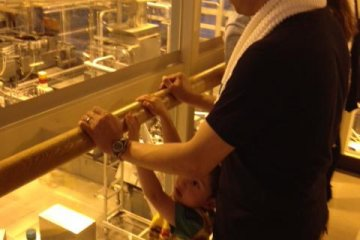 My son and husband gaze through a window overlooking the beer production machinery.