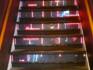 The neon staircase transport visitors to the bar on the upper level.