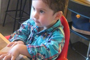 My son seated in the high chair.