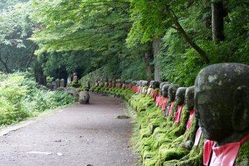 74 Jizo statues lined up along the riverside path