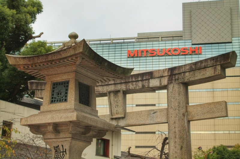 <p>Stone lantern and gate of Kego Shrine with Mitsukoshi department store in the background</p>