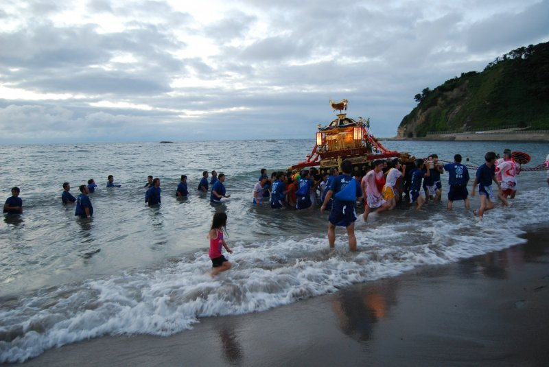 At the Okutsuhime Shrine festival young local men carry the portable shrine into the ocean.