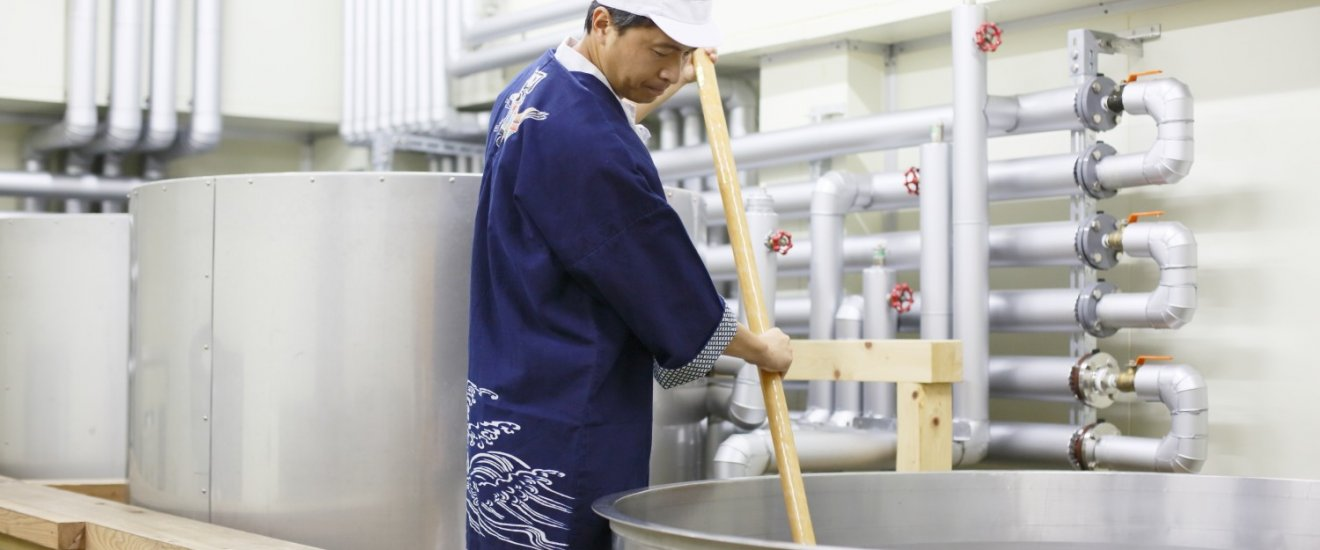A workers stirs a vat of sake mash in a Chiba brewery