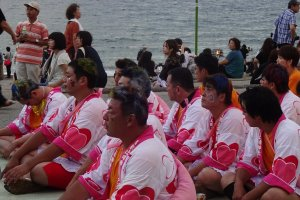 Dressed in women's clothes and make up on their faces, the guys wait for the blessing from a Shinto priest