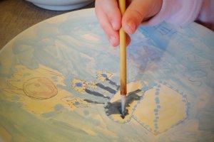 Seorang tamu cilik mencoba melukis di atas tembikar