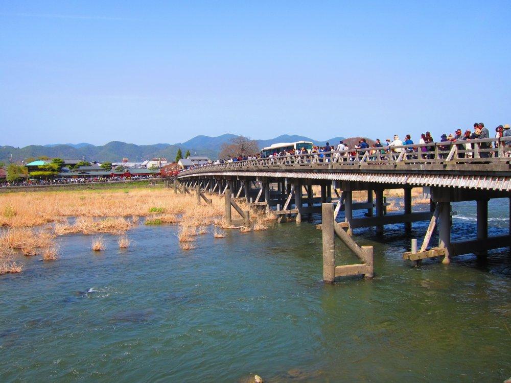 Arashiyama's iconic Togetsukyo Bridge packed with visitors.