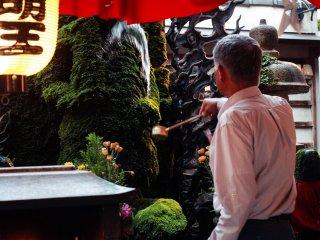 Un homme s'assure d'avoir bien arrosé la tête du Fudô