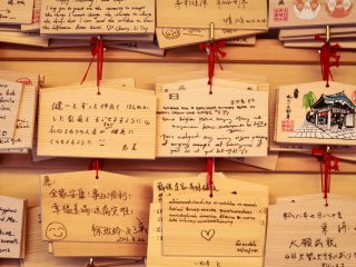 Les visiteurs écrivent leurs souhaits sur ces plaques de bois puis les accrochent