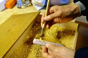 The craftsmaster adheres the gold leaf to the box lid by brushing with gold dust