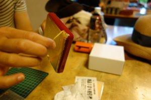 Một người tham gia workshop đang cẩn thận bóc lớp băng keo khỏi tác phẩm mà mình thiết kế