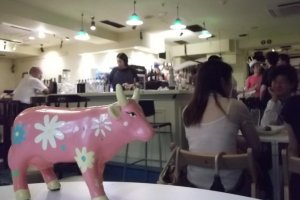 A pink cow watching over the action at the bar