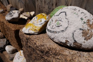 Many rocks with cute cat designs line the small streets